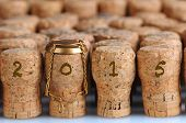 Closeup of a large group of Champagne corks, that fill the frame with the date 2015. Selective focus on the front row. One cork has the metal cage. Horizontal format.