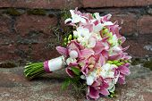 Bouquet from orchids, roses, irises and other flowers on a natural background.