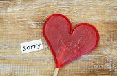 Sorry card with heart shaped lollipop on wooden surface