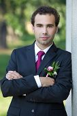 image of boutonniere  - The groom with boutonniere of peony. Groom standing near column. ** Note: Visible grain at 100%, best at smaller sizes - JPG
