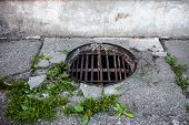 pic of manhole  - Manhole with the homemade metal armature cover in the cracked concrete and asphalt surface - JPG