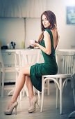 image of restaurant  - Fashionable attractive young woman in green dress sitting in restaurant - JPG