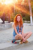 Red haired young women sitting on skateboard with her legs crossed backlit by sun