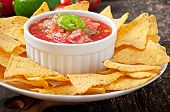 stock photo of nachos  - Mexican nacho chips and salsa dip in bowl on wooden background