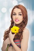 Portrait of beautiful girl in studio with yellow chrysanthemum in her hands. Sexy young woman