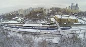 MOSCOW, RUSSIA - NOVEMBER 27, 2013: Train at snow-covered railway platform with a pedestrian bridge in the city, aerial view