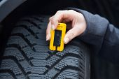 a young woman is measuring the tread depth of her car tire. the correct depth in the tread of a tire can prevent accidents.