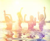 Group of happy teen girls playing in water at the beach on sunset. Beauty and joyful teenager friend
