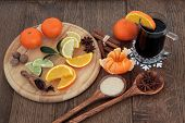 Christmas mulled wine ingredients of citrus fruit and spices over oak background.