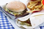 stock photo of junk food  - Various tasty junk food on table closeup photo - JPG