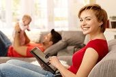 Happy young woman using tablet pc at home, family playing at background.