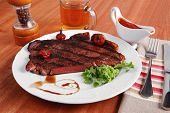 rural design new york meat style beef steak fillet on white plate with hot chili pepper served with