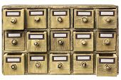primitive wooden apothecary or catalog cabinet with partially open drawers and blank labels in bronz