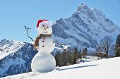 foto of snow capped mountains  - Snowman against Alpine panorama  - JPG