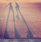 shadow of two people play fighting in the street toned with a retro vintage instagram filter