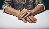 Senior Woman's Hands Clasped On A Table