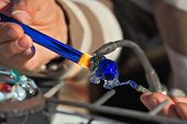 TEL AVIV, ISRAEL - FEBRUARY 11, 2012: Delicate work of the glass blower. The Artist-glass blower produces a graceful tiny figure of an elephant from color glass.