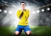 unhappy soccer or football player is down on his knees on stadium