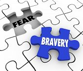 Bravery word on a puzzle piece about to fill the word Fear conquering adversity and being bold and c