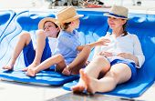 Mother and her kids relaxing having great time sailing at luxury yacht or catamaran boat