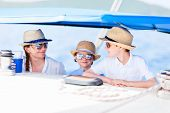 Mother and her kids having great time sailing at luxury yacht or catamaran boat