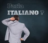 Composite image of thinking businessman against blue chalkboard, Do you speak Italian?