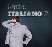 Composite image of thinking businessman against blue chalkboard, Do you speak Italian?