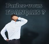 Thinking businessman scratching head against blue chalkboard, Do you speak French?