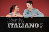 Young couple looking at each other while leaning on a wall against blackboard on wall, Do you speak Italian?