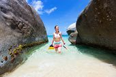 Young woman with snorkeling equipment at tropical beach among granite boulders at Virgin Gorda, Brit