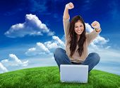 Woman looks straight ahead as she celebrates in front of her laptop against green field under blue sky
