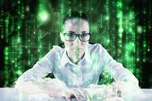Businesswoman typing on a keyboard against lines of green blurred letters falling