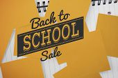 Back to school sale message against yellow paper strewn over notepad