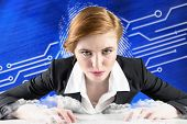 Redhead businesswoman sitting at desk typing against fingerprint on digital blue background
