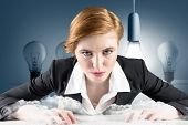 Redhead businesswoman sitting at desk typing against five light bulbs in a row with one lit up
