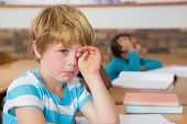 stock photo of upset  - Upset pupil sitting at his desk at the elementary school - JPG