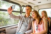 friendship, travel, summer vacation, technology and people concept - smiling couple with smartphone