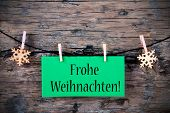 pic of weihnachten  - A Green Hanging Tag with the German Words Frohe Weihnachten which means Merry Christmas on wooden Background - JPG