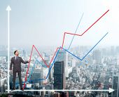 business, development and people concept - smiling man holding graph line over chart and cityscape b