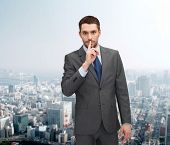 business, gesture and people concept - young businessman making hush sign over city background over