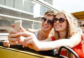 friendship, tourism, summer vacation, technology and people concept - smiling couple with smartphone