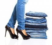 stock photo of outerwear  - Pile of blue jeans isolated on white - JPG