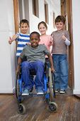 Disabled pupil with his friends in classroom at the elementary school