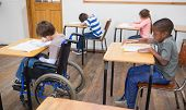 Disabled pupil writing at desk in classroom at the elementary school