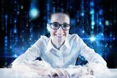 Businesswoman typing on a keyboard against lines of blue blurred letters falling