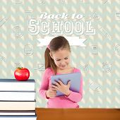 Cute girl using tablet against red apple on pile of books