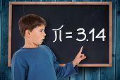 Cute boy pointing against blackboard on wooden board