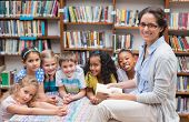 stock photo of classmates  - Cute pupils and teacher reading in library at the elementary school - JPG
