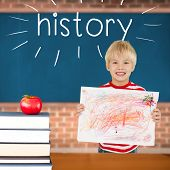 The word history and cute boy showing his art against red apple on pile of books in classroom