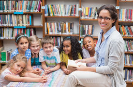foto of librarian  - Cute pupils and teacher reading in library at the elementary school - JPG